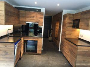 Vue globale droite d'une cuisine en bois foncé moderne avec bandeaux led encastrés dans meubles hauts