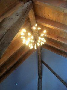 Lustre arbre lumineux sous charpente du chalet
