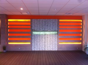 Vue de face du mur intérieur avec bandeaux led sur fond orange oranges et cailloux blancs entourés d'étagères bois et terrasse en bois noir