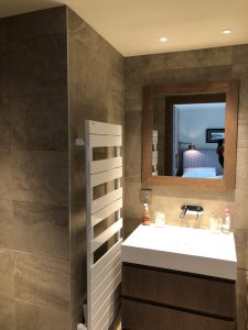 salle de bain avec spots au plafond et radiateur sèche-serviette électrique