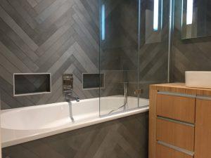 Salle de bains carrelage chevrons gris avec niches et baignoire