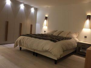 Chambre avec lit double et appliques en bois moderne
