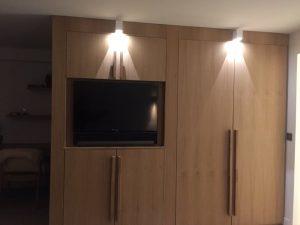Mur de la chambre avec télé encastrée et spots blancs carrés