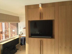 Mur de la chambre avec télé encastrée et spot carré blanc