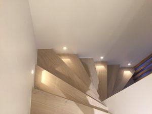 Escaliers en bois descendants avec spots encastrés au mur