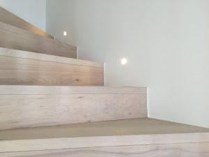 Escaliers en bois montants avec spots encastrés au mur