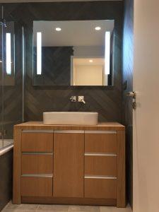 Salle-de-bains avec meuble en bois et carrelage gris en chevrons